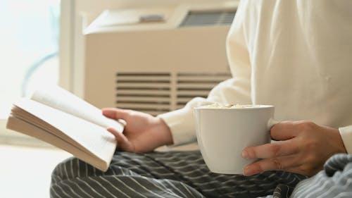 책을 읽는 동안 커피 음료를 들고 사람