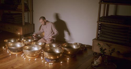 A Man Playing Music With Himalayan Bowls