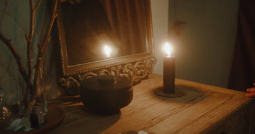A Lighted Black Candle In Front Of A Mirror