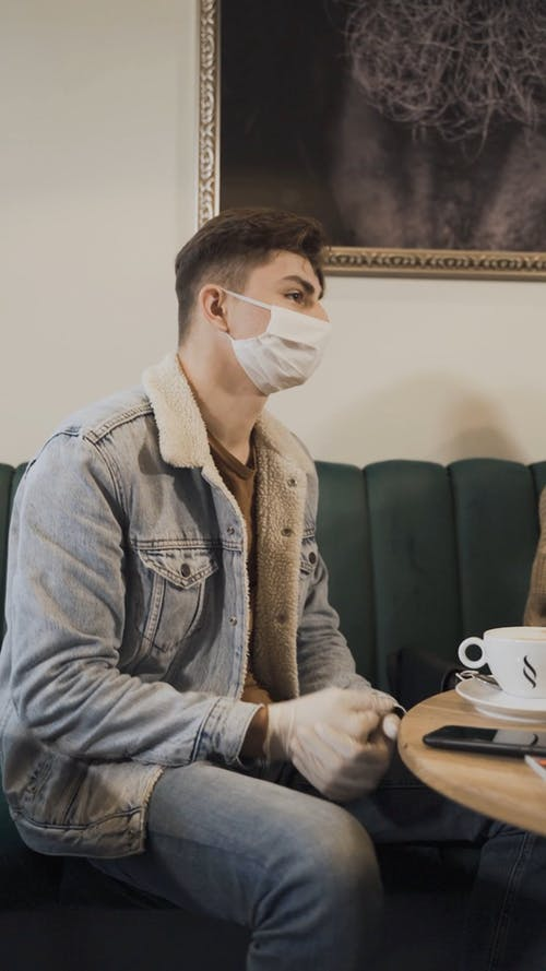 A Man Sitting in the Coffee Shop while Wearing Face Mask