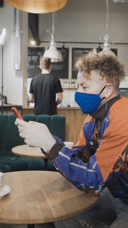 A Man in Face Mask is Texting Inside a Cafe