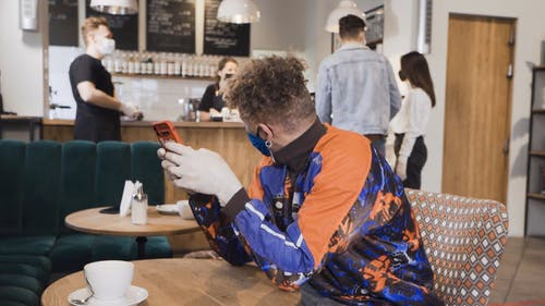 A Man Using a Smartphone in a Cafe