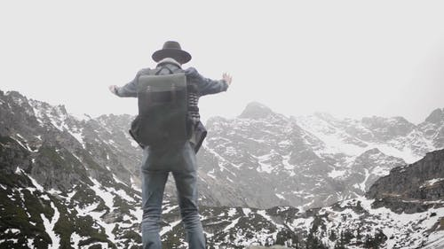 Man Standing on a Rock Facing Snow Capped Mountains