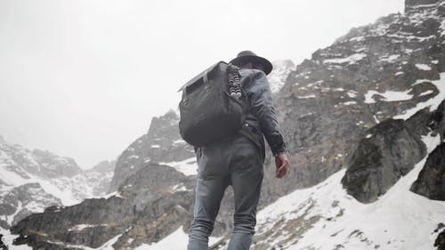 A Backpacker Man Standing on Mountain Cliff