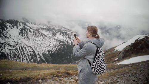 Woman Taking Pictures of the Snowy Mountains