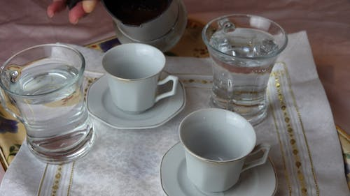 Person Pouring Black Coffee in the Cups