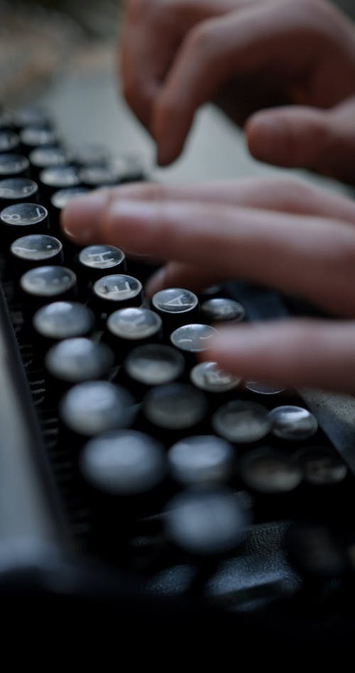 Close up View of a Person Typing on the Typewriter