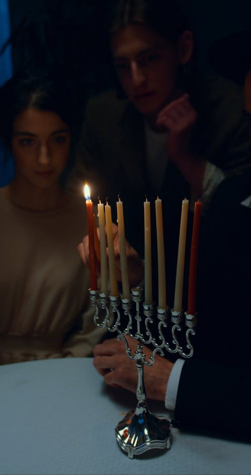Man Lighting A Candle At Hanukkah Celebration