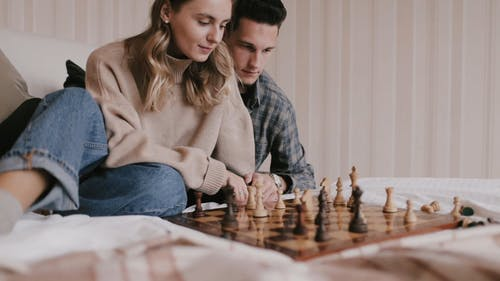 People Playing Chess While Sitting on the Bed