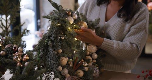 Women Putting Christmas Lights on Christmas Wreaths