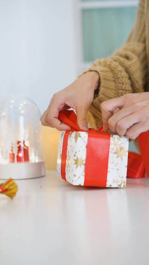 Close-up Shot of a Person Wrapping a Christmas Present