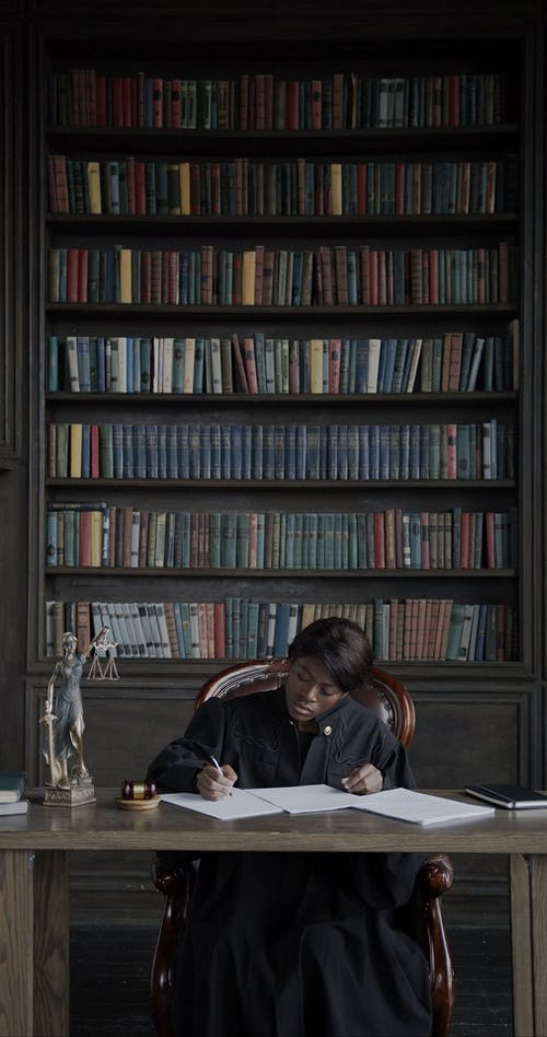 A Woman Writing on the Notebook with a Book- Filled Shelf Behind