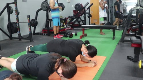 Women Wearing Face-mask Planking at the Gym