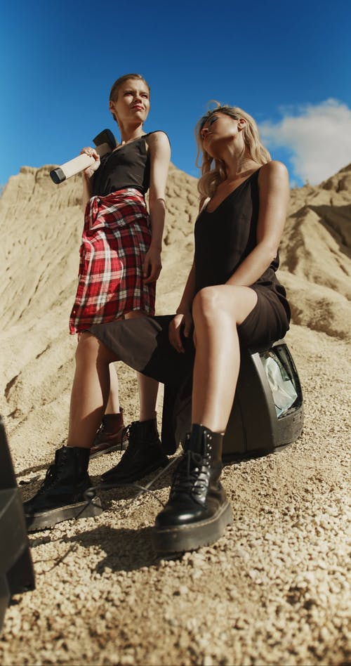 Fashionable Women Wearing Leather Boots Posing in the Desert