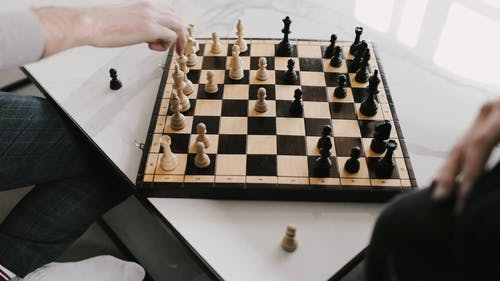 Two Men Playing Chess in the Table