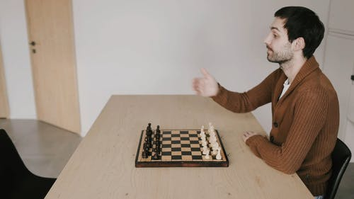 A Man Inviting Another Man to Play Chess