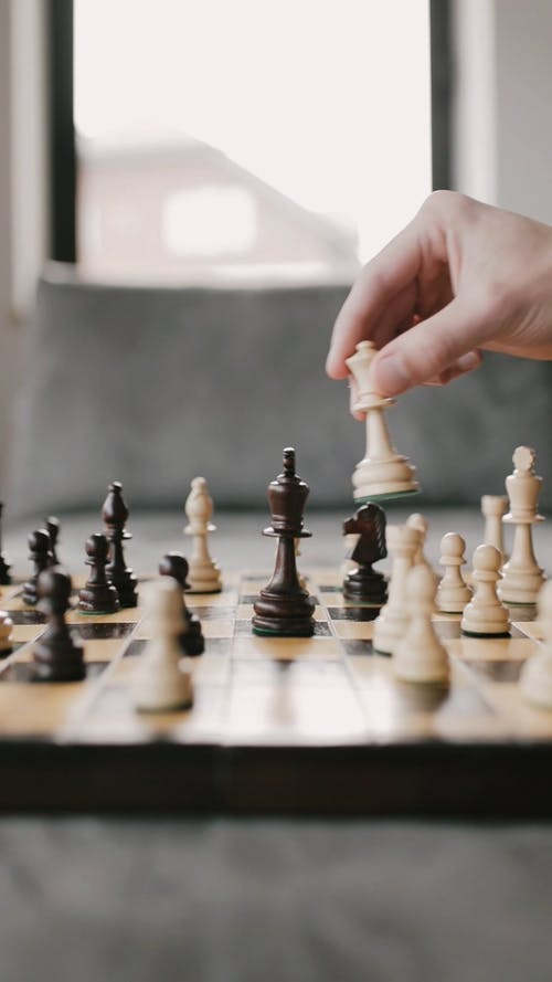 A Person Moving a Chess Piece on the Board