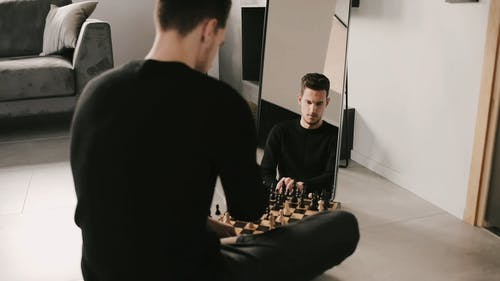 A Man Playing Chess in Front of a Mirror