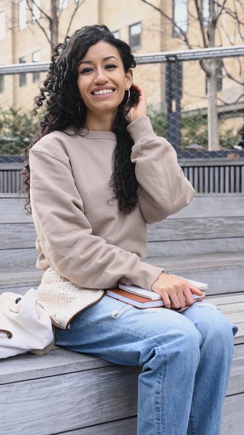 Young Woman Sitting on a Wooden Bench