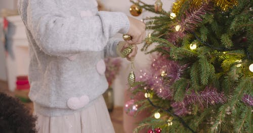 A Little Girl Decorating Their Christmas Tree