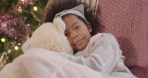 A Sleepy Girl Hugging Her Teddy Bear