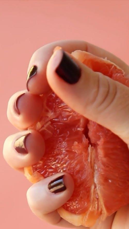 A Person Squeezing a Grapefruit