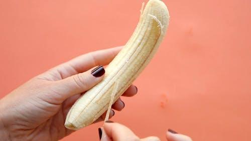 A Person Peeling a Banana