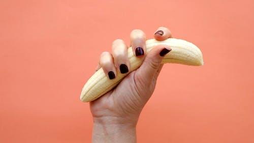 A Person Crushing a Peeled Banana