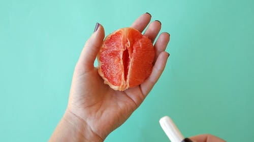 Tampon Being Inserted Into Sliced Citrus Fruit
