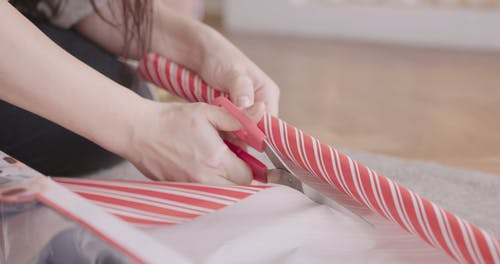 A Woman Cutting A Gift Wrapper