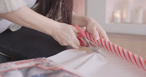 A Person Cutting A Gift Wrapper