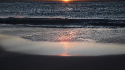 Sea Waves Over the Sunset
