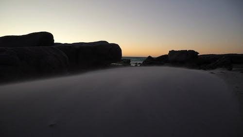 Wind Passing Through the Sand Between Rock Boulders