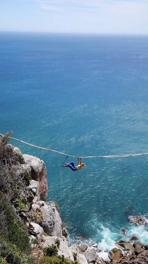 Person Hanging on a Rope Over Sea and Rock Boulders