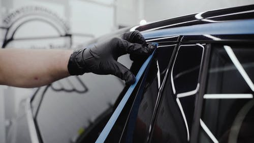Man Putting Tape on the Side of the Car Window