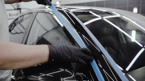 Man Putting Tapes on the Car