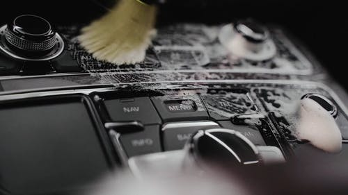 Person Cleaning the Car Interior with a Brush and a Cleaning Product