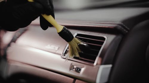 Person Cleaning the Car Aircon