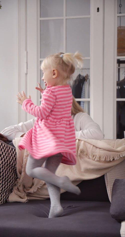 Happy Child Twirls Around While Mom Watches