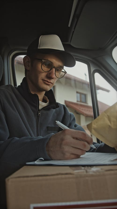 Man Writing Down Parcel Details in a Delivery Van