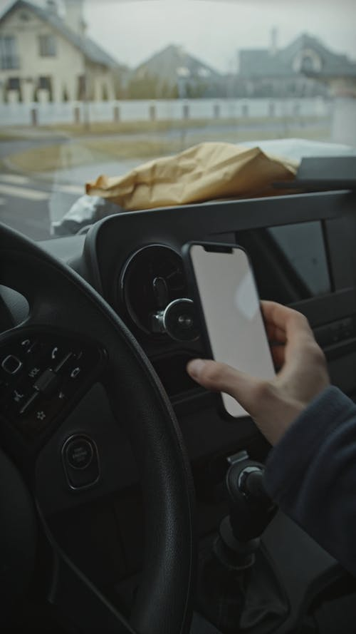 Courier Boy in Delivery Van Working with Mobile Phone