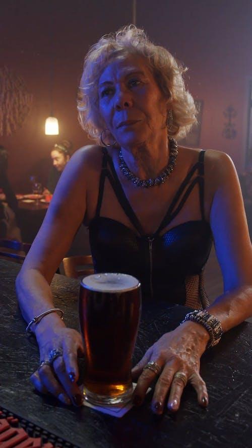 An Elderly Woman Sitting on a Bar Counter