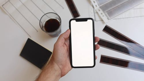 Person Holding an iPhone with a Blank Screen
