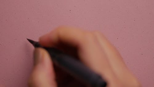 Person Doing Calligraphy in Pink Background