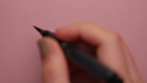 A Person Doing Calligraphy on a Pink Paper