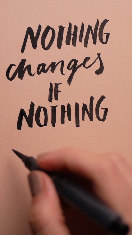 A Person Writing the Word Changes on a Paper