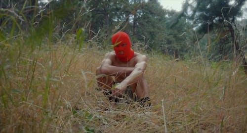 Man in Ski Mask Sitting in the Grass