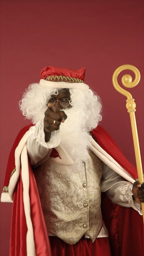 A Finger Pointing Santa Claus With A Cane