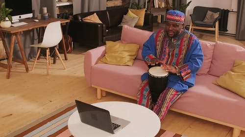 Video Of Man Playing Djembe In Front Of Laptop