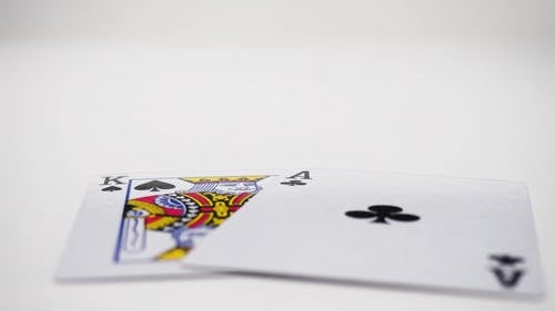 Close Up View of Playing Card and Casino Chips Tossed in the Table